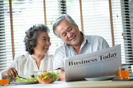 Entspannendes asiatisches Seniorenpaar, das morgens im Haus zusammen mit Frühstück spricht. Pensionierung. Standard-Bild