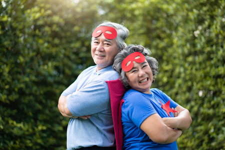 Asian Senior couple in Superhero costume relaxing and smiling with arms crossed at the park outdoor togetherness. Copy space. Looking camera. Imagens