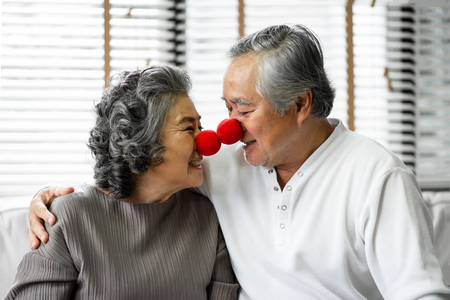 Funny Asian Senior Couple are playing red clown noses together. Smiling Grandfather and Grandmother in sweater having fun at their house. Retirement.