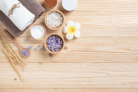 Spa products on wood background with Copy space. Cosmetic bottles, towels, wooden spoon, salt, soap, Plumeria Flower, barley