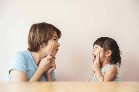 Happy Asian Kid e la sua insegnante si divertono con le matite all'asilo. Archivio Fotografico