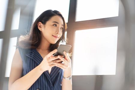 La mujer de negocios asiática moderna está utilizando el teléfono celular en la oficina. Diseñador de sexo femenino atractivo que sonríe y que se coloca cerca de una ventana.