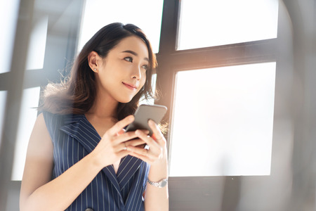 Modern Asian business woman is using cell phone in the office. Attractive Female designer smiling and standing near a window. 免版税图像 - 121634491