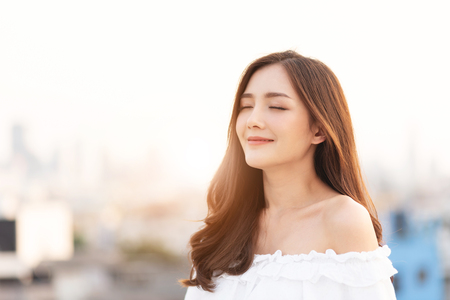 Beautiful Asian Woman is breathing fresh air. Smiling Female is standing on top of house roof over city background at outdoor. Relaxation, Eyes closed. Stock Photo