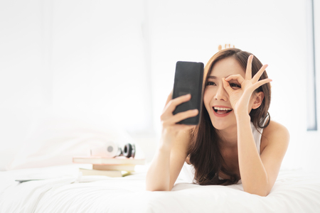 Happy Asian Beautiful female having fun with cell phone or mobile phone while lying on her bed. Cheerful girl is making video call with smartphone at her white bedroom. Communication with technology.
