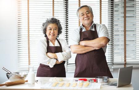 Porträt eines lächelnden asiatischen Seniorenpaares in braunen Schürzen mit verschränkten Armen, Großvater und Großmutter, die sich auf das Backen von Keksen am Feiertag vorbereiten Blick in die Kamera