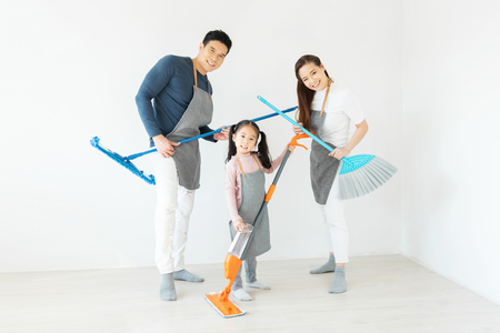 Having Fun. Happy Asian Family dancing and holding cleaning equipment like playing guitars in a white room.