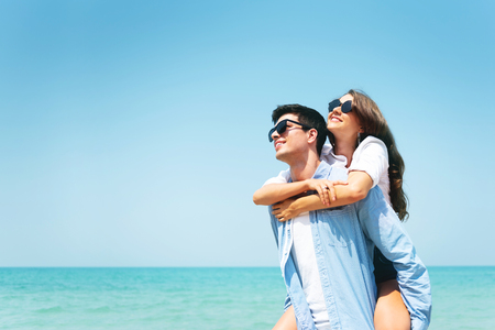 Happy Young couple wear sunglasses having fun on blue sky and the beach. Copy space. Piggyback ride.