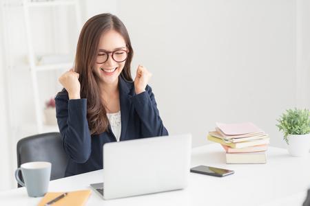 Eccitata donna d'affari asiatica dopo aver cercato un lavoro con un laptop in ufficio. Le donne di successo indossano occhiali con gesto di vittoria nella stanza bianca. Celebrazione.