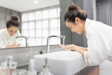 Le portrait d'une belle fille asiatique se lave le visage au lavabo dans sa salle de bain à la maison.