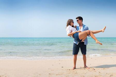 Homme portant une femme dans ses bras, Couple amoureux sur la plage.
