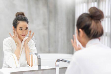 Chiuda sul ritratto di bellezza di una bella donna ridente che applica schiuma per lavarsi il viso e guardarsi allo specchio. Spa per la cura della pelle relax. Crema mattina e notte. Archivio Fotografico