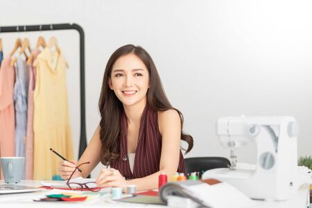 Successful of Young woman Fashion Designer is sitting and smiling. Happy, Relaxing Asian Female is working at her office. Startup Small business entrepreneur, SME.