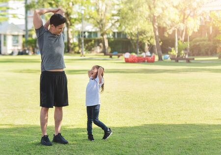 Asian father and his daughter stretching their arms and shoulders before exercising. Workouts and lifestyles concept. Happy family life and Health care concepts. Nature and Outdoors. Kid and dad having Fun with sport day.