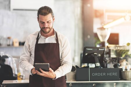 Male barista holding and looking at digital tablet at the coffee shop or restaurant cafe. Startup of small business entrepreneur owner.