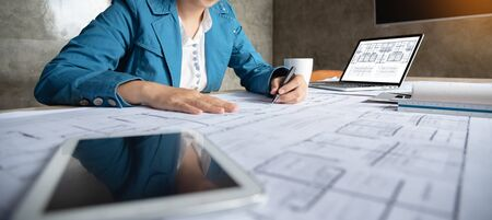 Woman Architect designer drawing on blueprints at the office.