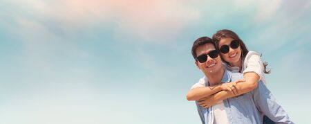 Happy Young couple wear sunglasses having fun on blue sky and the beach. Copy space. Piggyback ride. Web banner, panoramic. Фото со стока