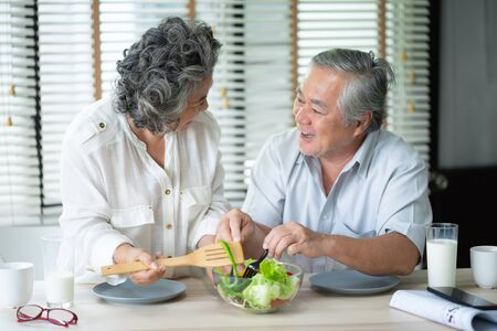 Happy Asian Senior couple doing healthy  salad at their house together.