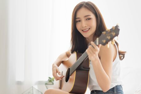 Pretty Asian woman is practicing guitar with copy space. Relaxing girl with the instrument in the white room at the house.