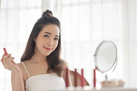 Beautiful Asian Female in white vest holding a red or pink lipstick and looking at camera. Happy woman applying makeup. Blogger, Cosmetics, Hairstyle.