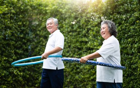 Asian Senior Couple in white shirt exercising with hula hoops at outdoor park together. Фото со стока