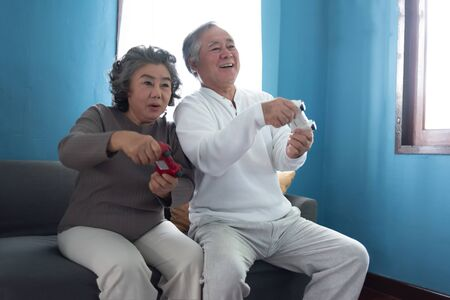 Happy Asian Senior Couple playing video games together.