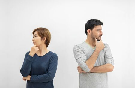 Portrait of young couple standing separately with arms crossed and thinking something on white isolated background. divorce, separated concept.