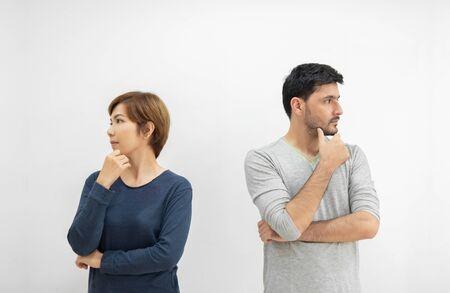 Retrato de pareja joven de pie por separado con los brazos cruzados y pensando en algo sobre fondo blanco aislado. divorcio, concepto separado.