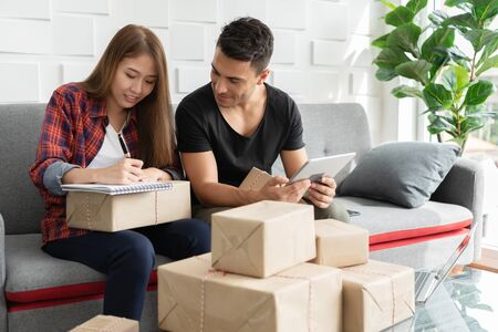 Happy young couple are preparing cardboard boxes products for their small business online at the house. 版權商用圖片