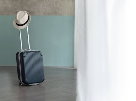 Suitcase with male hat on pastel blue and bare wall background. Holiday, Vacation and travel concept. Copy space.