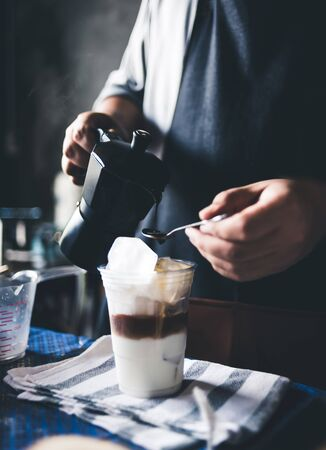 Barista making iced coffee. Male wear dark blue Apron Preparing Latte with milk on counter.