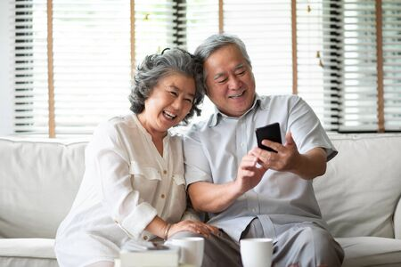 Asian senior Couple Laughing and using cell phone technology at their home.