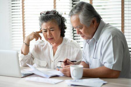 Pareja mayor asiática seria pensando en sus deudas con ordenador portátil. Ahorro, Finanzas, Gastos mensuales con Jubilación.
