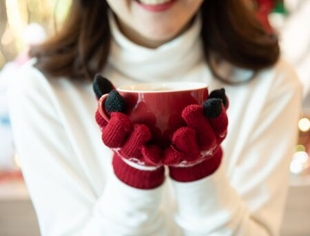 Smiling Asian woman wear white clothes and red gloves holding a cup of coffee in winter day. Christmas.