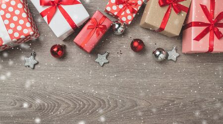 Christmas with gift boxes, snowflakes, silver stars, bells, glitters and bauble balls on wooden background. Copy space.