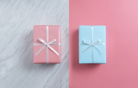 Top view of pink and blue gift boxes on white marble and pink isolated background. Christmas, Birthday and New year concept.