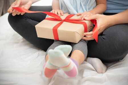 Child daughter unwrapping gift box with her mom on bed in their bedroom togetherness.