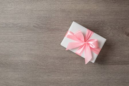Top view of white gift box with pink ribbon on wooden background with copy space.