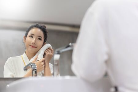 Portrait of Asian Female is touching her face with a towel. Skincare spa relax. Woman in bathrobe washing her face and looking at the mirror in a bathroom. Morning and night cream beauty. Reklamní fotografie