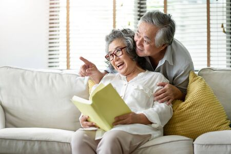 Happy Asian Senior couple are relaxing at the house with retirement. Copy space. Grandfather and Grandmother looking to the window together. Reklamní fotografie