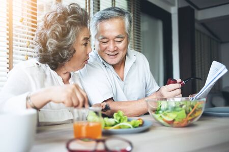 Asian couple enjoying with salad. Retirement, Healthy food. Фото со стока