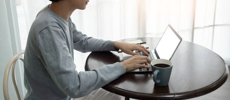 Asian Young man in sweater is using laptop computer on round wooden desk  in his workplace at his house. Typing, Job searching, Connection with wireless technology.