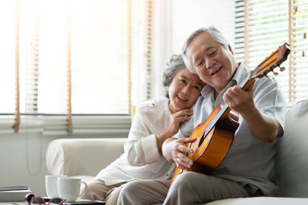 Happy Asian senior Couple enjoying with singing and playing guitar together. Having fun.