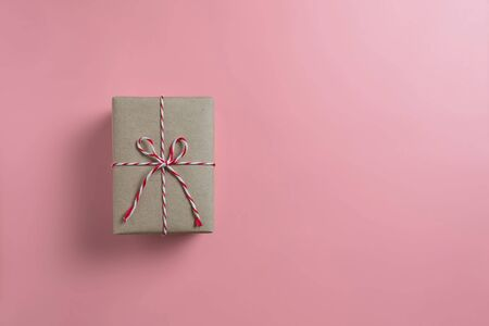 Top view of brown gift box with red rope on pink isolated background. Christmas, Birthday and New year concept. Reklamní fotografie