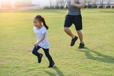 Happy Asian little kid is running with her family at outdoor park. Start, Exercise, Workout, Race, Competition, Victory, Goals concepts. Reklamní fotografie