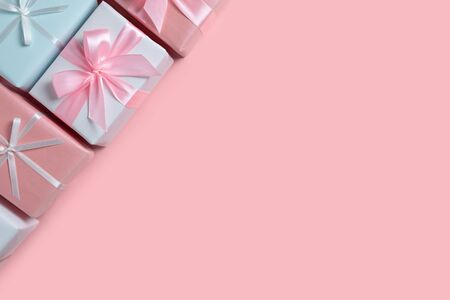 Colorful gift boxes at the corner on pink isolated background with copy space. Christmas, Birthday and New year concept. Reklamní fotografie