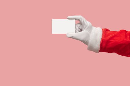 Santa Claus hand holding plastic credit card over isolated background. Shopping, Sales, Giving Gift for Black Friday, Christmas and New Year 2019 concepts.