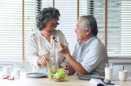 Glückliches asiatisches älteres Paar, das zusammen gesunden Salat in ihrem Haus tut und isst. Liebhaber, Ruhestand, Wellness.