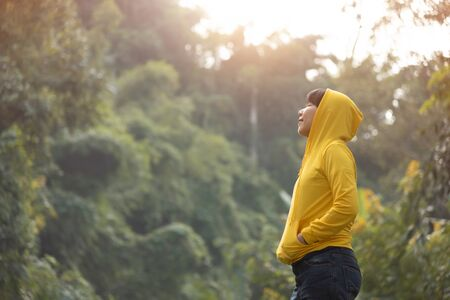 Happy Asian woman traveler in yellow sweater with hood is standing and breathing fresh air over nature background.