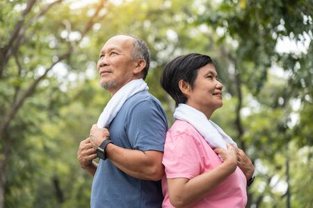 Portrait of Asian Senior couple standing over green nature background. Elderly Man and woman exercising at park outdoor together.